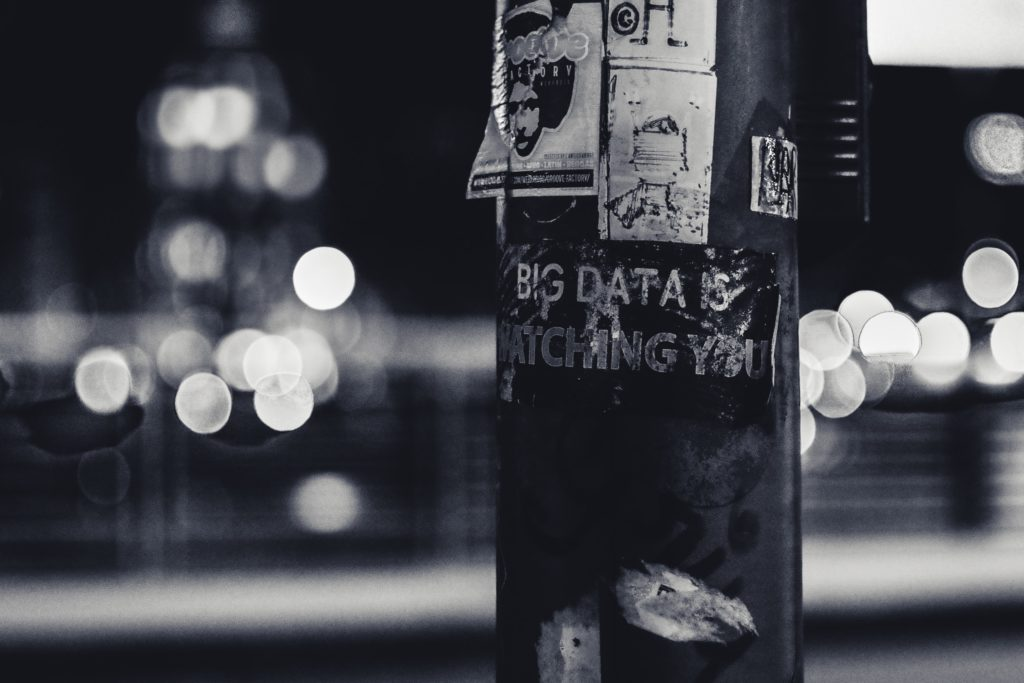 "image of a lamppost covered in posters. One poster says ""Big Data is watching you"""